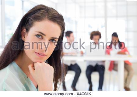 Employé de bureau attrayant et pensée looking at camera Banque D'Images