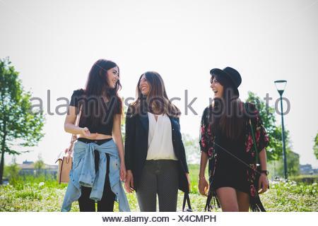 Trois jeunes amies bavarder tout en flânant dans le parc Banque D'Images