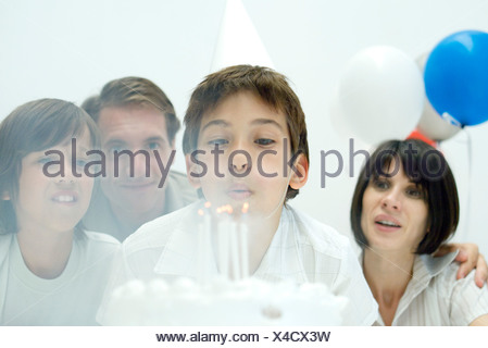 Boy blowing out candles on cake, regardant Banque D'Images
