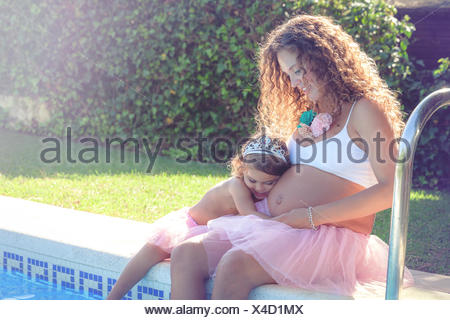 Pregnant woman sitting with daughter by swimming pool Banque D'Images