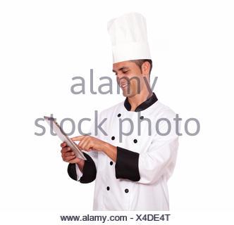 Portrait d'un jeune homme cuisiner avec tablet pc sur fond isolé. Banque D'Images