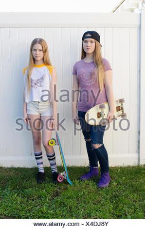 Portrait de deux jeunes sœurs dans jardin skateboarder Banque D'Images