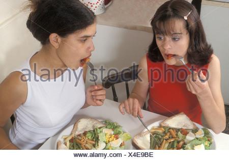 Deux teenage girl friends pâtes repas ensemble Banque D'Images