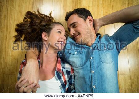 Jeune couple lying on floor dans leur chambre Banque D'Images