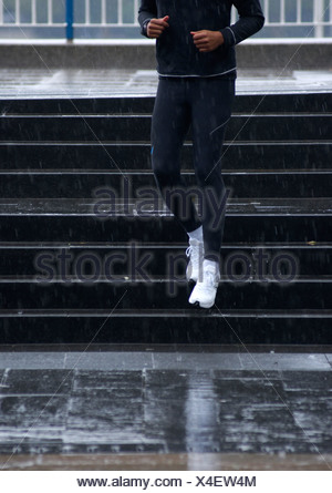 L'homme venant des étapes dans la pluie Banque D'Images