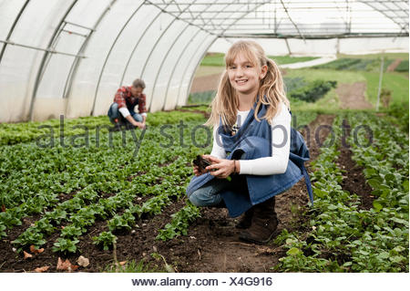 Smiling blonde girl in greenhouse
