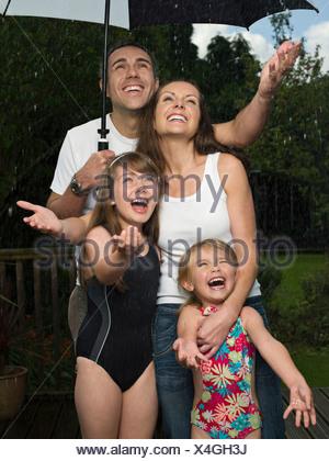 Une famille sous un parapluie sous la pluie Banque D'Images