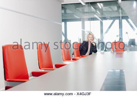Femme assise sur chaise orange dans la salle de conférence Banque D'Images