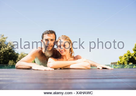 Heureux couple leaning on pool edge Banque D'Images