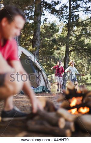 Les enfants courent de père en camping Banque D'Images
