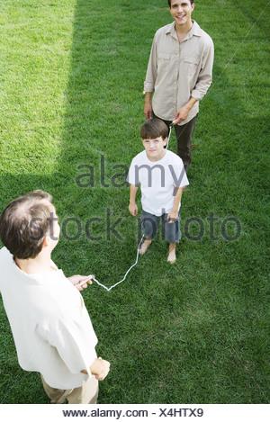 Garçon jouant sauter à la corde avec deux hommes, smiling at camera Banque D'Images