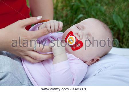 Un bébé de quelques mois, s'accrochant aux doigts de sa mère
