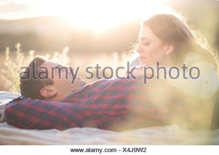Jeune couple lying outdoors with relaxing Banque D'Images