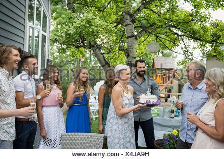 Fille surprenant père avec gâteau d'anniversaire garden party Banque D'Images