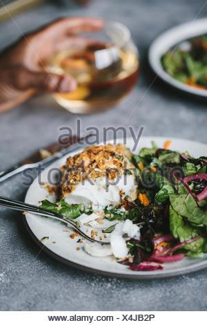 A moitié mangé du poisson frit avec quelques salade est photographié par le côté. Banque D'Images