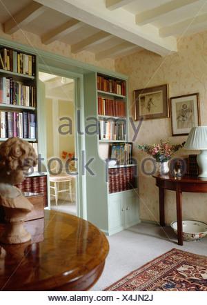 Poutres apparentes peintes en blanc en pays hall avec couleur bleu-vert des étagères de chaque côté de la porte et à l'ancienne table console Banque D'Images