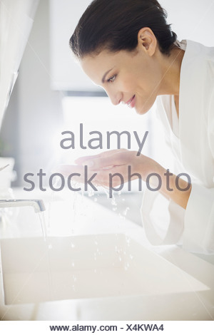 Femme en peignoir aux projections d'eau sur le visage Banque D'Images
