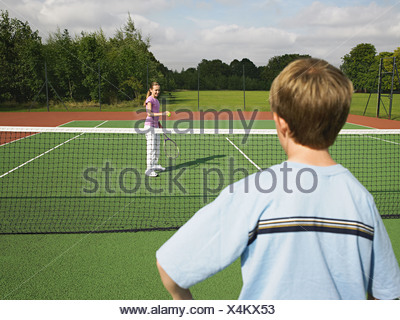 Boy and girl playing tennis Banque D'Images
