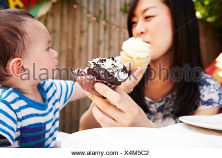 La mère et le fils de l'alimentation chaque autres cupcakes Banque D'Images