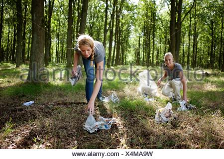 Deux jeunes femmes picking up trash Banque D'Images