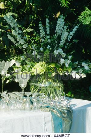 Still-Life de delphiniums blanc vase en verre sur la table de jardin avec des verres de vin Banque D'Images