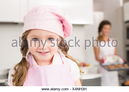 Petite fille portant un tablier rose et chefs hat smiling at camera Banque D'Images