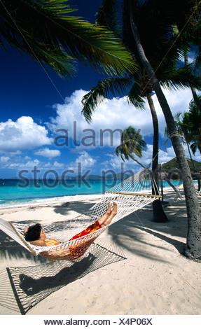 Femme dans un hamac sous les palmiers sur une plage sur Peter Island, British Virgin Islands, Caribbean Banque D'Images