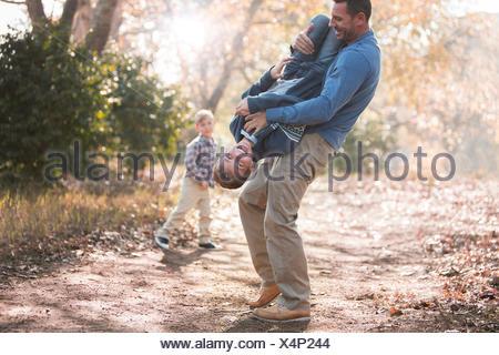 Père Fils ludique de levage à l'envers sur le chemin dans les bois Banque D'Images