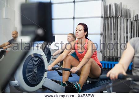 Femme à l'aide d'une machine à ramer en salle de sport Banque D'Images