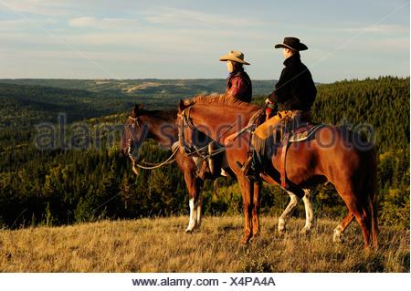 Cowboy et cowgirl assis à cheval, à la recherche dans la distance, de la Saskatchewan, au Canada, en Amérique du Nord Banque D'Images