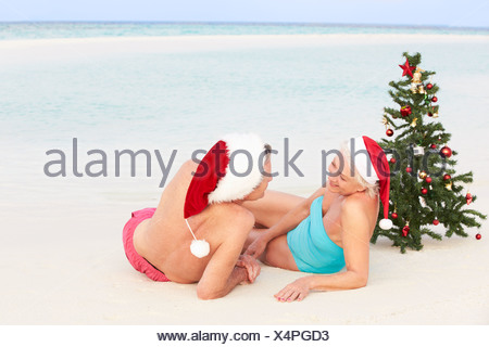 Senior Couple Sitting On Beach With Christmas Tree et chapeaux Banque D'Images