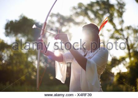 Femme mature dans les bois en vue de l'arc et de la flèche Banque D'Images