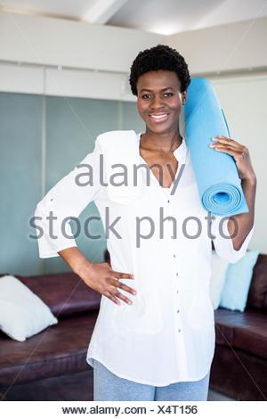 Portrait of happy pregnant woman holding exercise mat Banque D'Images