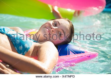 Fille sur le flotteur dans piscine Banque D'Images