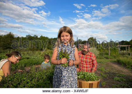 Portrait of Girl holding bouquet de feuilles sur family herb farm Banque D'Images