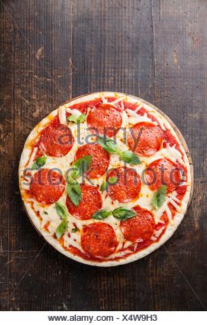 Pizza au pepperoni, avec des feuilles de basilic sur table en bois Banque D'Images