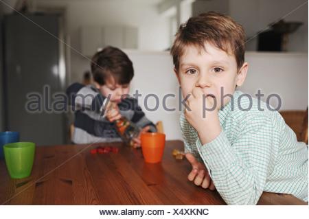 Garçons jouant avec des bonbons à la table Banque D'Images
