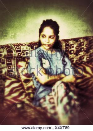 Femme assise dans un canapé et la pensée Banque D'Images