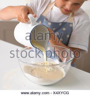 Jeune garçon 6-7 ans verser le lait en farine pour faire la pâte à crêpes Banque D'Images