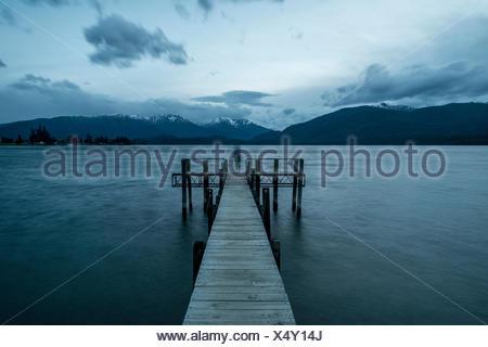 Ciel nuageux sur les montagnes, silhouette debout sur dock, Lac Te Anau, Southland, Nouvelle-Zélande Banque D'Images