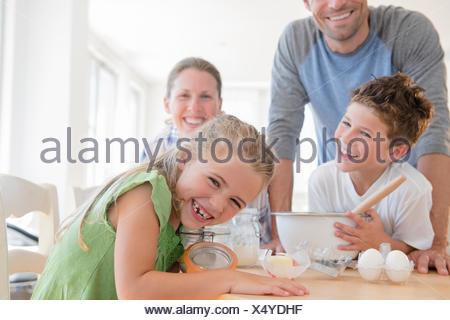 Famille avec deux enfants (6-7, 8-9) de préparer des aliments, rire Banque D'Images