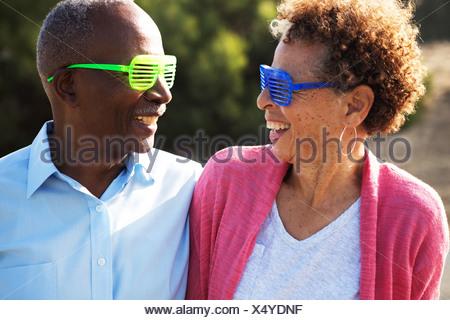 Couple portant des lunettes en plastique bleu et vert Banque D'Images