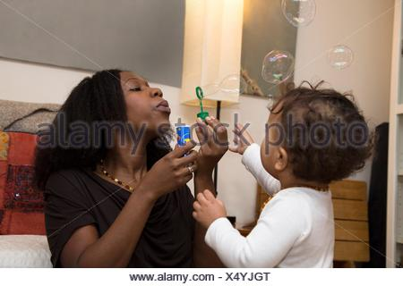 Mid adult woman and toddler daughter blowing bubbles Banque D'Images
