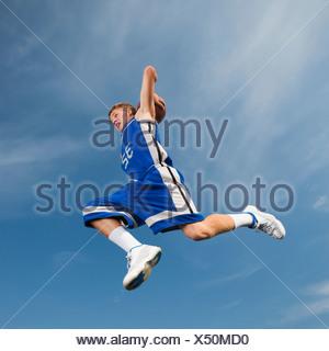Joueur de basket-ball d'Adolescent jeter l'air mi-basket-ball Banque D'Images
