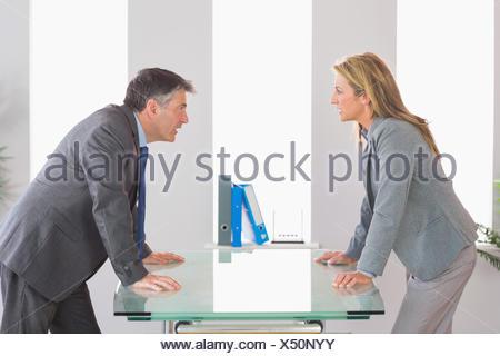 Deux angry businessman arguant de chaque côté d'un bureau à l'office de tourisme Banque D'Images