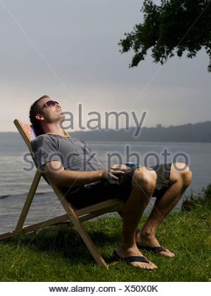 Homme assis dans la chaise de jardin en plein air Banque D'Images