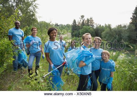 Portrait de bénévoles transportant des sacs poubelles dans la zone Banque D'Images