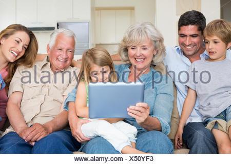Famille multigénérationnelle using digital tablet Banque D'Images