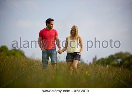 Un jeune couple marche main dans la main à travers un champ en été Banque D'Images