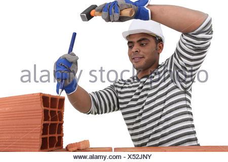 Mason en utilisant un burin sur la brique Banque D'Images